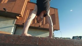 Young acrobatic man performs a handstand on the curb outdoors at sunset. Slow motion stock footage