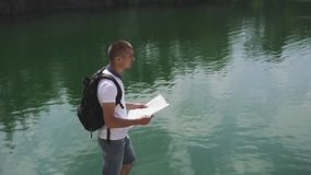 Young active backpacker checking with map near water surface of mountain lake at sunny day stock footage