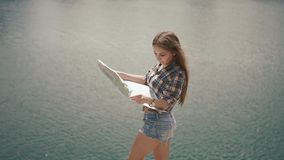 Young active backpacker girl checking with map near water surface of mountain lake at sunny day stock video footage
