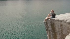 Young active backpacker girl relaxes by resting on mountain rock upon large water surface of mountain lake stock video