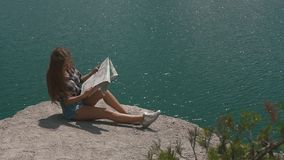 Young active backpacker girl rests on mountain rock upon large water surface of mountain lake and looking to map stock video