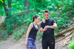 Young active couple looking at smart watch heart Royalty Free Stock Photos