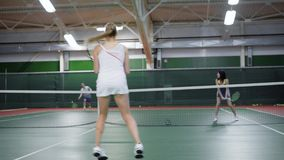 Young active couples are playing tennis on indoor court. Two men and two woman wearing sport clothes jumping holding. Two young active couples are playing tennis stock video