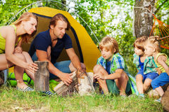 Young active family making camp fire in the woods Stock Images