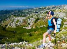 Female in mountains look in binocular Stock Photos