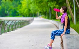 Young active fitness woman with mat and bottle of Royalty Free Stock Image