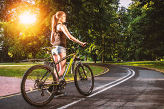 Young active girl with bicycle in park. Stock Photography
