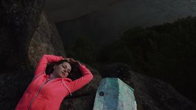 Young active girl relaxes by resting on mountain rock at evening. Green trees and river steam as background below.  stock footage
