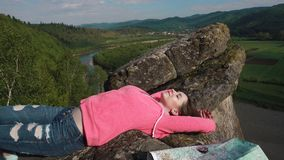 Young active girl relaxes by resting on mountain rock. Green forest and river valley under blue sky as background stock footage