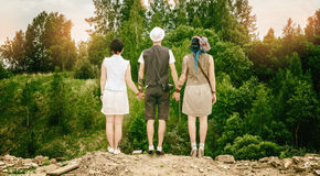 Young active guy and girls hipsters hold hands over an abyss Royalty Free Stock Photos