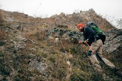 Young active male hiking in mountains with travel backpack. Traveler bearded man trekking and mountaineering during his journey. Travel, people, sport and stock photo