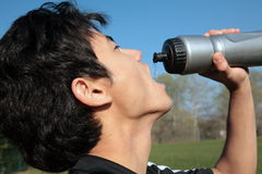 Young active man drinking water. Portrait of a young active man drinking water out of a bottle outdoors Royalty Free Stock Photo