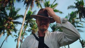 A young active man with a hat with a mustache among the coconut palms wipes sweat from his forehead and then greets the
