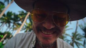 A young active man in a hat with a mustache in yellow glasses among the coconut trees sends greetings to the camera stock video
