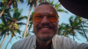 A young active man in a hat with a mustache in yellow glasses among the coconut trees sends greetings to the camera stock video footage