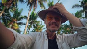A young active man in a hat with a mustache in yellow glasses among the coconut trees sends greetings to the camera stock footage