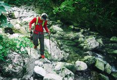 Young active man hiking with trekking poles. On stones along mountain river. Panoramic travel background royalty free stock photography