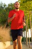 Young active man jogging outdoors Stock Photos
