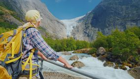 Young active woman admiring the beautiful nature of Norway - looking up at the Briksdal glacier. A woman traveler looks at the famous Briksdal glacier in Norway stock photos