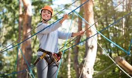 Young active woman doing a high ropes course. Outdoor activity. Nice attractive joyful woman wearing a mountain helmet and safety equipment while doing a high Royalty Free Stock Photo
