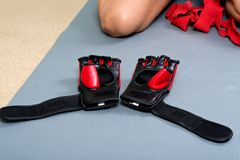 Young active woman getting prepared for exercises wrapping her hands with red bandage tape. In homemade gym, fitness royalty free stock photography