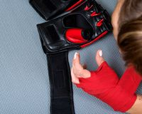 Young active woman getting prepared for exercises wrapping her hands with red bandage tape. In homemade gym, fitness royalty free stock photos