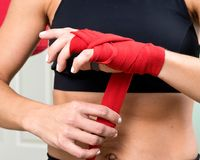Young active woman getting prepared for exercises wrapping her hands with red bandage tape. In homemade gym, fitness royalty free stock photo
