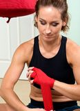 Young active woman getting prepared for exercises wrapping her hands with red bandage tape Stock Images