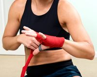 Young active woman getting prepared for exercises wrapping her hands with red bandage tape. In homemade gym, fitness stock photos