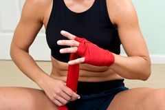 Young active woman getting prepared for exercises wrapping her hands with red bandage tape. In homemade gym, fitness stock image
