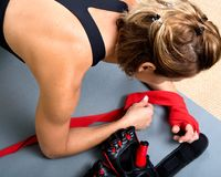 Young active woman getting prepared for exercises wrapping her hands with red bandage tape Royalty Free Stock Photos