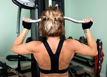 Young active woman and her shoulder, back and triceps workout Stock Photo