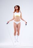 Young active woman with jump rope in studio.  Royalty Free Stock Photo