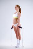 Young active woman with jump rope in studio.  Royalty Free Stock Photos