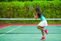 Young active woman playing tennis on tropical Stock Photography