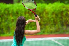 Young active woman playing tennis on tropical Stock Photo