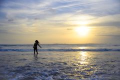 Young active woman on sea landscape sunset horizon with amazing sun and dramatic orange sky Stock Photo