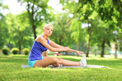 Young active woman sitting on an excercising mat and stretching Stock Images