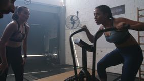 Woman training on air bike with trainers stock footage