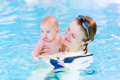 Young active woman swimming pool with baby boy Royalty Free Stock Images