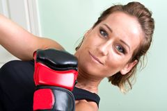 Young active woman workout: cardio kickboxing, punching bag. In homemade gym, fitness Royalty Free Stock Image