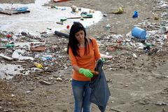 Young activist cleaning dirty beach in nature disaster Royalty Free Stock Photo
