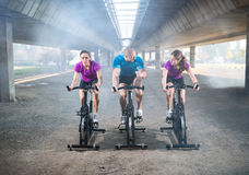 Young activity people exercising spin bike Royalty Free Stock Photography