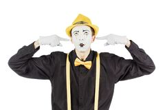 A young actor, a pantomime, closes his hands behind his ears, he stock images