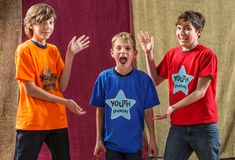 Young actor screams beside two friends. Young actor screams as his two friends pose for the camera on either side of him Stock Photo
