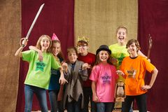 Young actors pose with costume pieces. Young actors holding costume pieces smile and pose for the camera Royalty Free Stock Photography