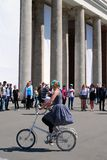Young actors performing in the Gorky park. A woman rides a bicycle. Stock Photos