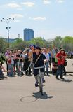 Young actors performing in the Gorky park. Wwoman and man ride a bicycle. Stock Photos