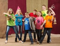 Young actors pose together with sword. Children at acting camp pose together with swords and trident Royalty Free Stock Image