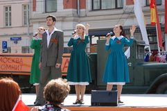 Young actors sing songs on stage. Young actors dressed in vintage clothes sing songs on stage in Moscow city center. Victory Day celebration on May 09, 2013 in Royalty Free Stock Image